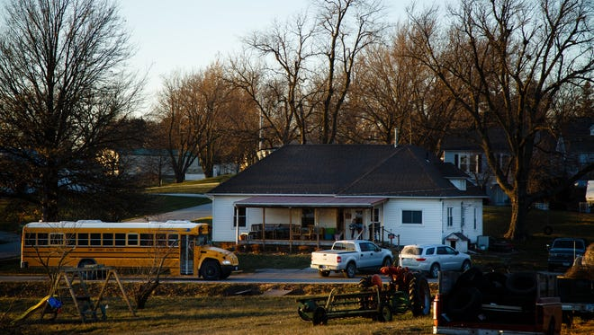 A school bus drops off Bailey Lillard, 9, and her brother Hunter, 5, at their home after school on Tuesday, Dec. 12, 2017, in Wiota. The two are Wiota's youngest residents and the only kids in town.