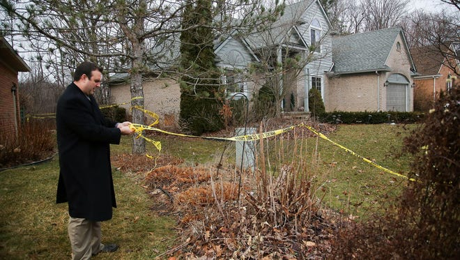 A Novi, Mich., police detective secures the police tape around a home where five Mexican immigrants died in a house fire in January 2016. Roger Tam, the owner of the home, was sentenced Thursday, Jan. 4, 2018, to nine months in prison for their deaths.