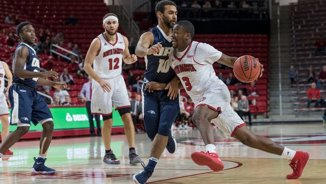 South Dakota's Triston Simpson drives past Oral Roberts' Sam Kearns on Wednesday night at the Sanford Coyote Sports Center.