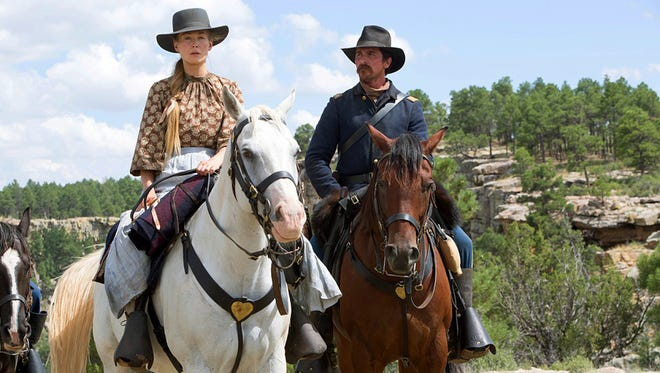 "Christian Bale (right) and Rosamund Pike hit a sorrowful trail in the Western ""Hostiles."""