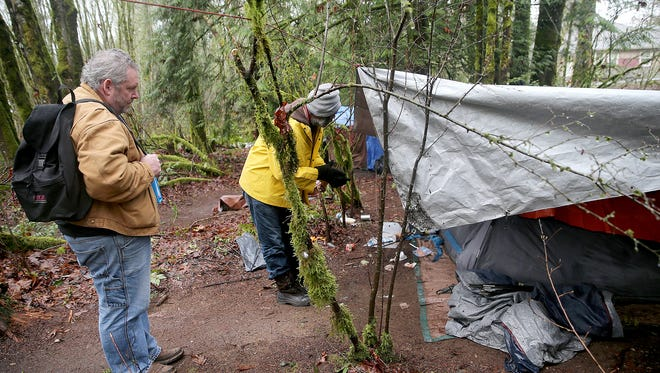 FILE PHOTO — Doug Washburn, left, from the Kitsap County Department of Human Services, counts residents of a homeless camp located on a forested property on Almira Drive in East Bremerton, during a previous point in time count.
