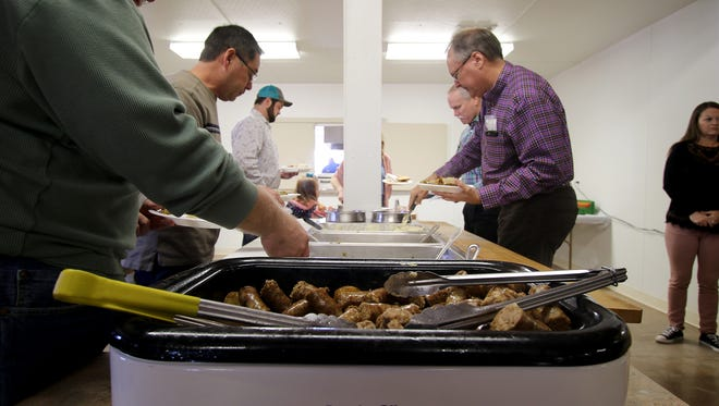 People go through the line filling their plates with sausage, green beans, corn, mashed potatoes and sauerkraut during the annual Scotland Sausage Feed Sunday, Feb. 4, 2018, at the Scotland Knights of Columbus hall.