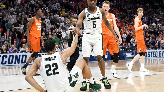 Michigan State's Cassius Winston, right, helps up teammate Miles Bridges during the second half on Sunday, March 18, 2018, at the Little Caesars Arena in Detroit. Syracuse beat Michigan State 55-53.