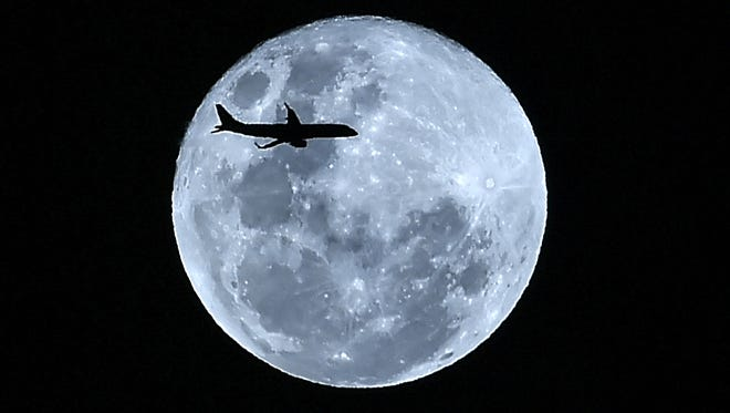 """A plane in flight is silhouetted against the """"super blue moon"""" over Cali, Colombia on January 31."""