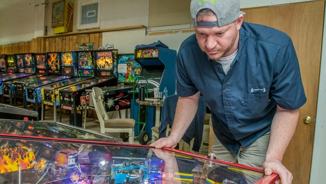 In this April 2018 photo, John Tomsich, of Youngstown, plays on an AC/DC pinball machine in Sharon, Pa. John comes to play in the weekly league and is rated one of the top 5 pinball players in the state of Ohio. (Cory Byknish /The Herald via AP)
