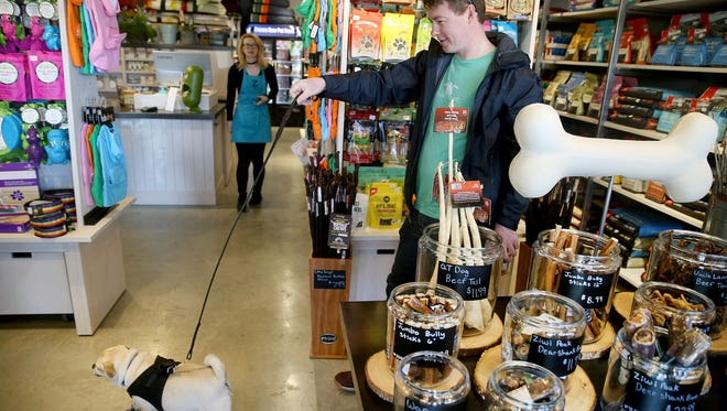 Jeremy Ghent shops with his dog Che at the new Z Bones Pet Mercantile at the Winslow Green, on Bainbridge Island. He is a regular visitor.