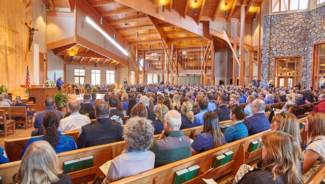 Attendees at Holy Family Catholic Church in Woodruff pay respects during a memorial service for medics and the pilot of a medical helicopter that crashed April 26.