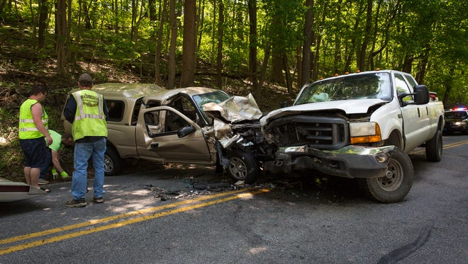 Crews clear debris and prepare to tow two vehicles at the scene of a crash with entrapment on the 6200 block of Old Hanover Road, Monday, May 7, 2018 in Heidelberg Township.