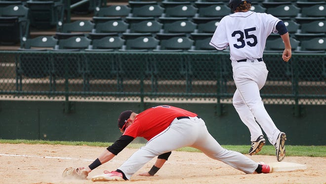 St. Cloud State's Mathew Meyer stretches to get the out at first against Augustana's Ryan Nickel in the NSIC baseball playoffs Thursday, May 10, at Sioux Falls Stadium.