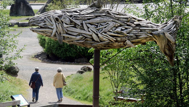 People walk back to the parking area at Fish Park in Poulsbo under the wooden fish sculpture.