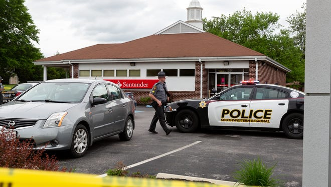State Police work at the scene of a police-involved shooting at a bank on the first block of West Hanover Street, Wednesday, May 30, 2018 in Spring Grove. According to a news release by State Police, Southwestern Regional Police were responding to a disturbance at the bank when an individual was shot by an officer. The individual is in stable condition at York hospital, the release states.