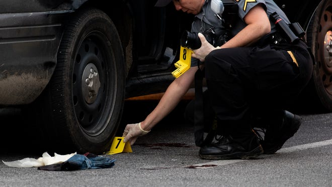 An officer with the State Police Forensic Services Unit places an evidence marker on a shell casing under the wheel of a Southwestern Regional Police car at the scene of a police-involved shooting at a bank on the first block of West Hanover Street, Wednesday, May 30, 2018 in Spring Grove. According to a news release by State Police, Southwestern Regional Police were responding to a disturbance at the bank when an individual was shot by an officer. The individual is in stable condition at York hospital, the release states.