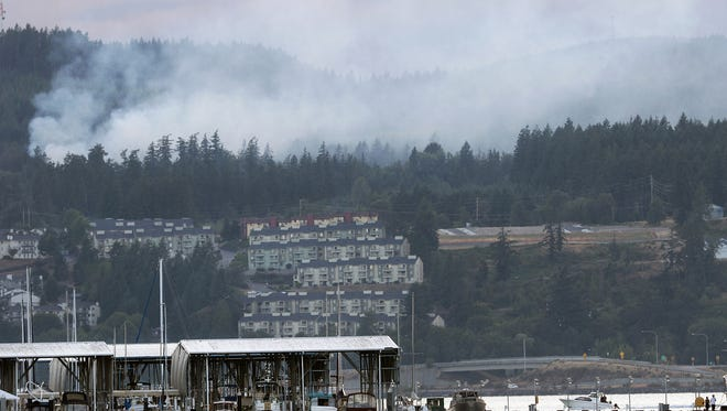 A fire burns in the Bremerton Watershed in a view from Port Orchard toward the marina on Wednesday evening.