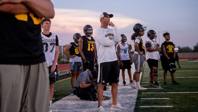Saguaro High School head football coach Jason Mohs (center) watches game drills on July 24, 2018, during the Saguaro High School Sabercats' first football practice of the 2018-2019 school year at Saguaro High School in Scottsdale, Arizona.