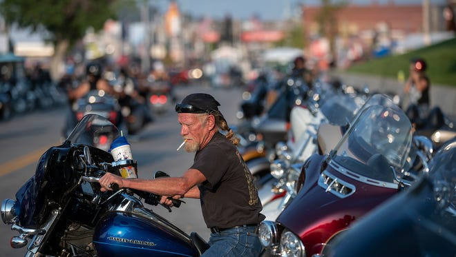 In this Saturday, Aug. 4, 2018, photo, Don Hudson, of Davison, Mich., parks his motorcycle along Main Street in Sturgis, S.D., during the 78th annual Sturgis Motorcycle Rally. (Ryan Hermens/Rapid City Journal via AP) (Ryan Hermens/Rapid City Journal via AP)