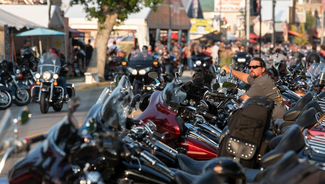 In this Saturday, Aug. 4, 2018, photo, Rob Gregory, of Knoxville, Tenn., sits on his motorcycle parked along Main Street in Sturgis, S.D., during the 78th annual Sturgis Motorcycle Rally. (Ryan Hermens/Rapid City Journal via AP)