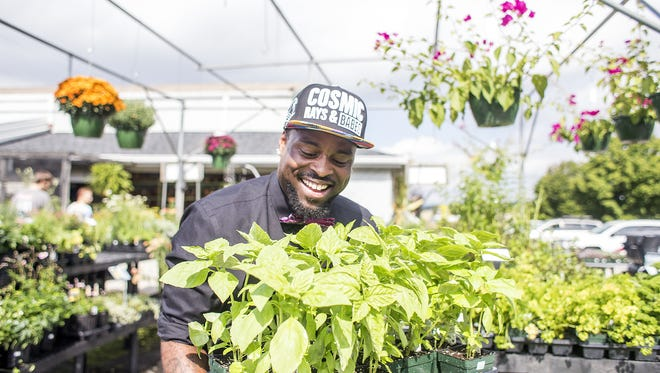 Clarence Robinson jokes around with a flat of sweet basil at the WNC Farmers Market in September.