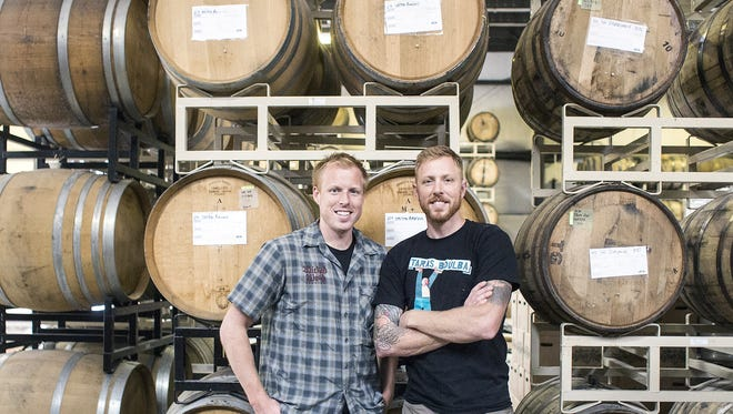 Luke, left, and Walt Dickinson, owners and brewers of Wicked Weed, stand in front of barrels inside their new Funkatorium on Coxe Avenue in Asheville, Wednesday, Sept. 17, 2014. The Funkatorium will have about 1,000 barrels of sour beer aging in its back shop with a tasting room up front for customers. The brother brewers said they plan on the new place becoming its own little brewery devoted mainly to sour beer. 9/17/14