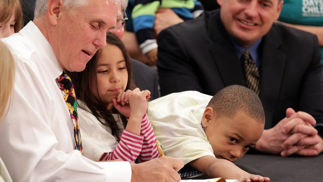 Gov. Mike Pence signs a bill to create a pre-K pilot program as 5-year-old Rosie Chavez and 4-year-old Tre Embry help with the pens that were later given to lawmakers who helped pass the bill.
