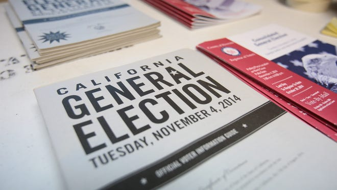 Stacks of election informational booklets are set out for Tuesday's election as precinct workers set up their room on Monday, November 3, 2014 at the Quality Inn in Palm Springs, Calif.