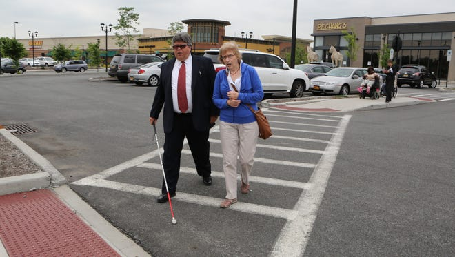 Joel V. Taveras walks with Jayne Malkin with the Association for the Visually Impaired, across a crosswalk in a parking lot at The Shops at Nanuet in June.