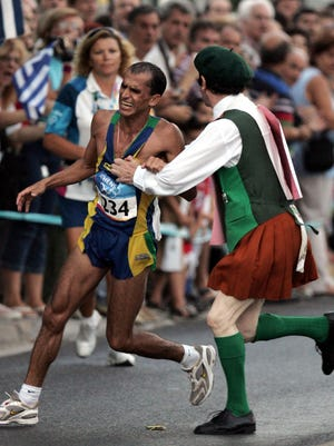 In this Aug 29, 2004, file photo, defrocked Irish priest Neil Horan, right, grabs Vanderlei Cordeiro de Lima of Brazil and knocks him into the crowd.