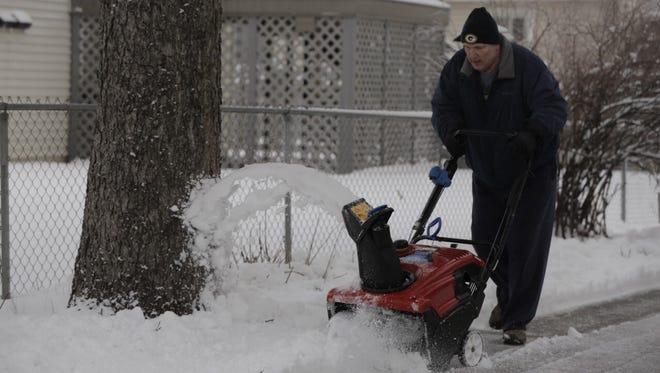 Jim Schroeder clears a path along Knapp Street  in Oshkosh Thursday.