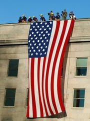 13 Sep 2001, Arlington, Virginia, USA --- Military service members render honors September 12, 2001 as fire and rescue workers unfurl a huge American flag over the side of the Pentagon during rescue and recovery efforts following the September 11 terrorist attack. The attack came at approximately 9:40 a.m. local time as a hijacked commercial airliner, originating from Washington's Dulles airport, was flown into the southern side of the building. Two other hijacked airliners were crashed into New York's World Trade Center and another airliner was crashed in rural Pennsylvania, near Pittsburgh.  REUTERS/U.S. Navy photo-Michael W. Pendergrass --- Image by © Reuters/CORBIS
