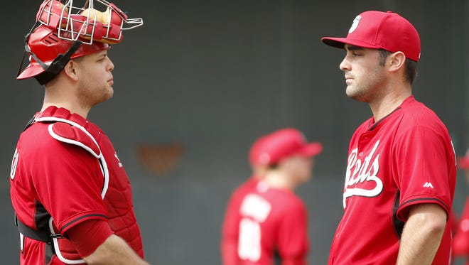 Reds pitcher Devin Mesoraco talks with pitcher Matt Magill during pitching drills at Spring Training, Sunday, Feb. 22, 2015, in Goodyear, Arizona.