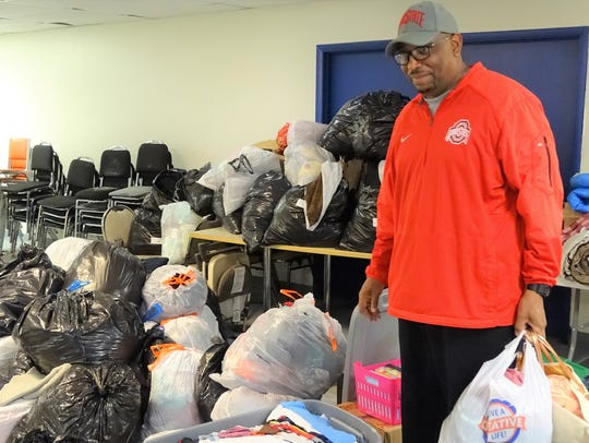 Pastor Corredon Rogers stands next to some of the donations