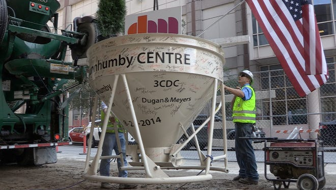 The last bucket of concrete is raised to the top of the dunnhumbyUSA headquarters Wednesday afternoon Downtown. The building required 60,000 tons of concrete and is expected to be completed in April.