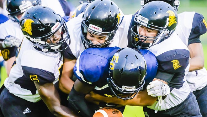 Several members of the Waverly defensive unit wrap up La'Tone Smith of Eastern at the line of scrimmage during their game Friday September 3, 2015 at Sexton High in Lansing. KEVIN W. FOWLER PHOTO