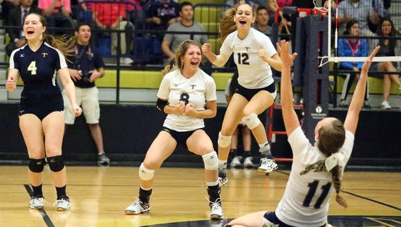 The Coronado volleyball team celebrates after scoring