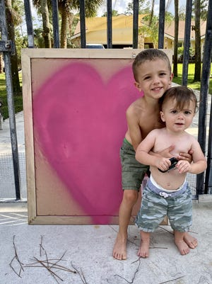 Michael and Maverick Zimmer, ages 4 and 1, respectively, stand next to a handmade heart sign in front of their Jupiter Farms home.