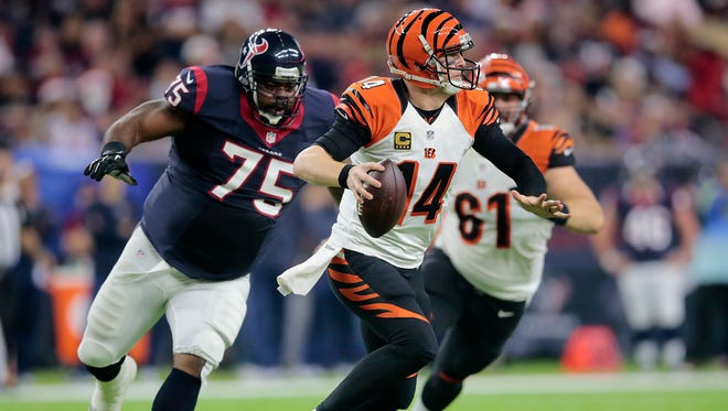 Cincinnati Bengals quarterback Andy Dalton (14) rolls out of the pocket as Houston Texans nose tackle Vince Wilfork (75) applies pressure in the first quarter during the Week 16 NFL game between the Houston Texans and the Cincinnati Bengals, Saturday, Dec. 24, 2016, at NRG Stadium in Houston, Texas. The Cincinnati Bengals lead 3-0 at halftime.