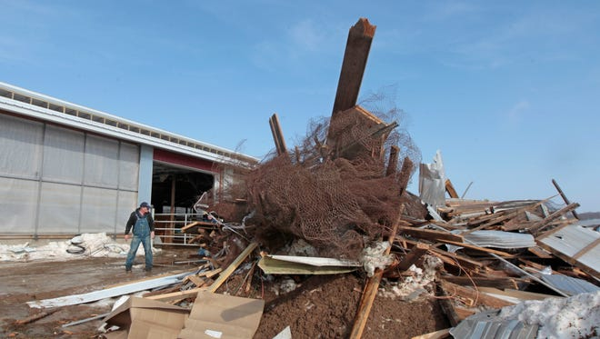 Henry Adams walks past a large pile of debris that was removed from inside his cattle barn following a roof collapse at his Black Brook Farm in Farmington Wednesday. Two separate sections of roof on his large cattle barn collapsed just weeks apart because of the snow during the exceptionally cold and snowy winter.