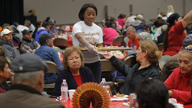 Volunteers serve Thanksgiving meals to El Pasoans in need Thursday at the El Paso Convention Center.
