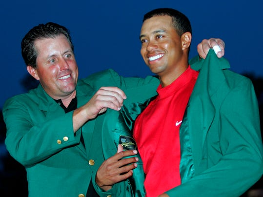 FILE - In tis April 10, 2005, file photo, Tiger Woods, right, gets the green jacket from Phil Mickelson, left, after winning the  Masters golf tournament at the Augusta National Golf Club in Augusta, Ga. (AP Photo/Morry Gash, File)