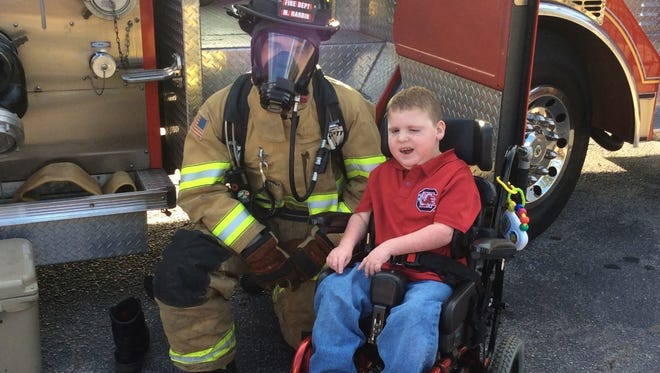 Student Carter Riddle enjoys visiting with a Williamston's volunteer fireman at Palmetto Elementary School.