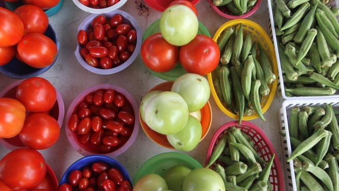 Locally grown tomatoes and okra are just two of the many vegetables sold Saturdays at the Market Square Farmers Market.