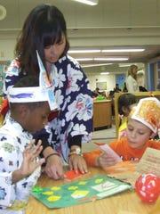 Teaching intern Kyoka Miyagi helps kindergartners Jason Huff, left, and Alex Granke with their origami during Friday's fall festival at Niji-Iro Japanese Immersion Elementary in Livonia.