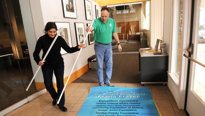 Nellie Doneva/Reporter-NewsSujata Shahane, left, and Rodney Goodman, right, prepare to hang a banner for the Marla Frazee exhibit at the NCCIL.