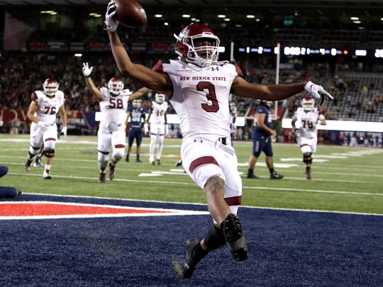 New Mexico State running back Larry Rose III (3) reacts after scoring a touchdown in overtime to defeat Utah State 26-20 in the Arizona Bowl NCAA college football game, Friday, Dec. 29, 2017, in Tucson, Ariz. (AP Photo/Rick Scuteri)