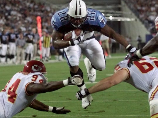 FILE - In this Aug. 5, 2000, file photo, Tennessee Titans running back Rodney Thomas (22) jumps between Kansas City Chiefs defenders Jonathan Jackson (94) and Kevin Sluder (62) to score a touchdown in the second quarter of an NFL football game in Nashville, Tenn. A Texas funeral home director says former Houston Oilers and Titans running back Thomas has died at age 41. Groveton Funeral Home owner Terry Cartwright says Thomas died Saturday, June 14, 2014, of an unknown cause and that an autopsy is underway. (AP Photo/Wade Payne, File)
