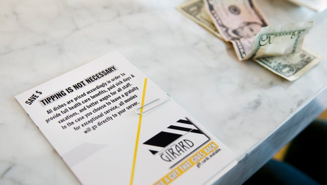 This card, presented with a bill, explains the no-tipping policy at Girard restaurant in Philadelphia on Tuesday, Nov. 25, 2014.   Servers there earn about $13 an hour. They also get sick time, vacation days and health insurance. Even being aware of the policy, some diners leave a tip for good service. The restaurant has reignited debate over working conditions in the food service industry.
