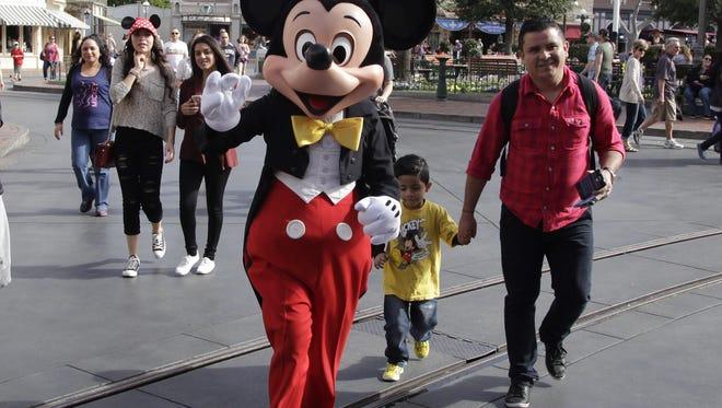 Jae C. Hong, AP Visitors follow Mickey Mouse for photos at Disneyland, Thursday, Jan. 22, 2015, in Anaheim, Calif.
