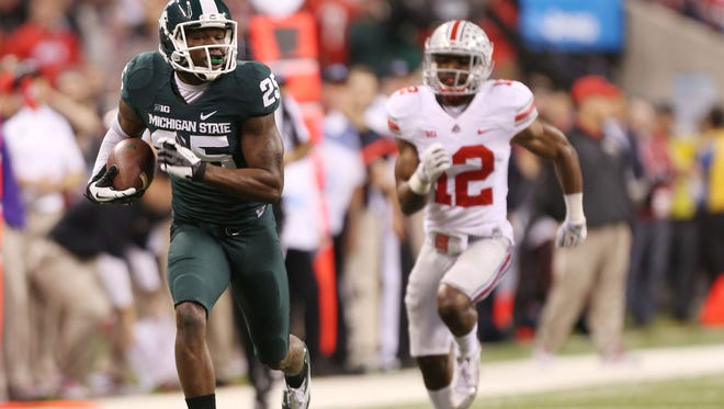 MSU receiver Keith Mumphrey (25) catches a pass and runs it in for a touchdown as Ohio State cornerback Doran Grant (12) gives chase during the 2013 Big Ten Championship game in Indianapolis.
