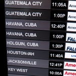 A sign shows the departure times for flights to Cuba at Miami International Airport on Dec. 19, 2014.