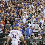 New York Mets fans cheer for starting pitcher Noah Syndergaard as he leaves the field after being ejected from Saturday's game during the third inning after throwing behind the back of the Dodgers' Chase Utley.