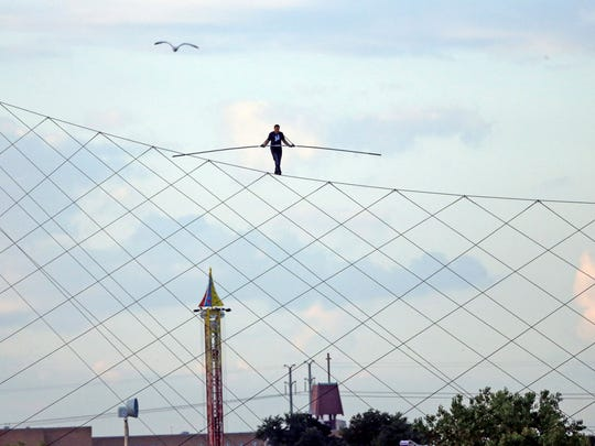 High-wire daredevil Nik Wallenda walks a tightrope above the  Milwaukee Mile Speedway at the Wisconsin State Fair in West Allis on Tuesday, Aug. 11, 2015.